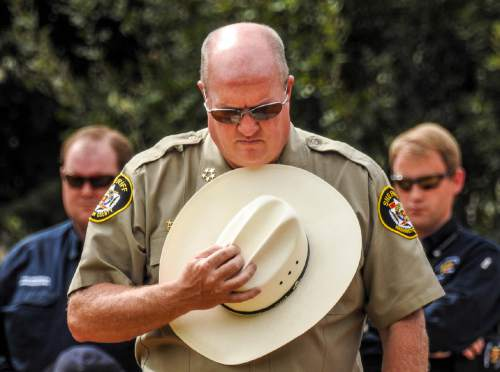 Trent Nelson  |  The Salt Lake Tribune Washington County Sheriff Cory Pulsipher bows his head at a memorial for the victims of a Sept. 14 flash flood. The memorial was held in Maxwell Park in Hildale, Saturday Sept. 26, 2015.