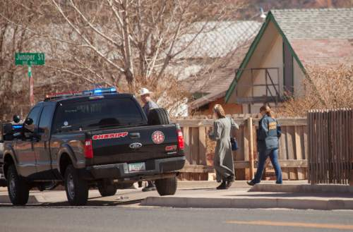 Law enforcement officers walk through Hildale, Utah on Tuesday, Feb. 23, 2016. Several top leaders from Warren Jeffs' polygamous sect were arrested Tuesday on federal accusations of food stamp fraud and money laundering marking one of the biggest crackdowns on the group in years. Lyle Jeffs, one of the 11 charged in the scheme, runs the day-to-day operations in the polygamous community. (Chris Caldwell/The Spectrum via AP)