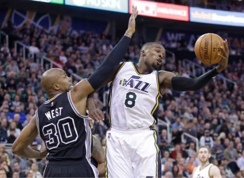 Utah Jazz guard Shelvin Mack (8) pulls down a rebound as San Antonio Spurs forward David West (30) defends during the second quarter in an NBA basketball game Thursday, Feb. 25, 2016, in Salt Lake City. (AP Photo/Rick Bowmer)