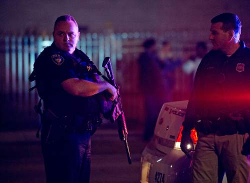 Lennie Mahler  |  The Salt Lake Tribune  A University of Utah police officer pulls his assault rifle out of the trunk in response to an angry crowd that formed after an officer-involved shooting at 200 South Rio Grande Street in Salt Lake City, Saturday, Feb. 27, 2016.