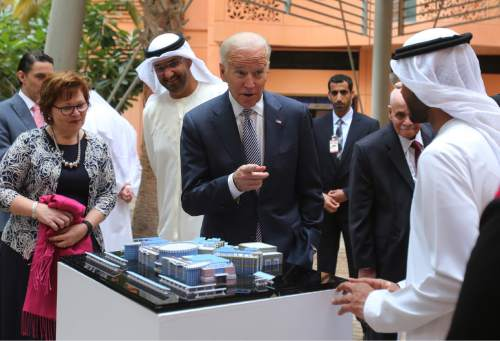 """Joe Biden, the U.S. Vice President, centre, points to one of the Masdar City employees as Sultan Ahmed Al Jaber UAE minister of state and the chairman of Masdar City, 3rd left, looks on during his first day tour in Abu Dhabi, United Arab Emirates, Monday, March 7, 2016. U.S. Vice President Joe Biden kicked off a Middle East tour Monday, vowing that the United States and its allies would """"squeeze the heart"""" and destroy the Islamic State group.  (AP Photo/Kamran Jebreili)"""