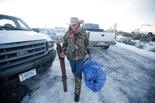 FILE - In this Jan. 6, 2016 file photo, Arizona rancher LaVoy Finicum carries his rifle after standing guard all night at the Malheur National Wildlife Refuge near Burns, Ore.  The FBI and Oregon State Police arrested the leaders of an armed group that has occupied a national wildlife refuge for the past three weeks during a traffic stop that prompted gunfire, and one death, along a highway through the frozen high country. The Oregonian reported that  Finicum was the person killed, citing the man's daughter.  (AP photo/Rick Bowmer)
