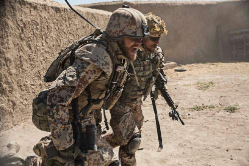 """   Magnolia Pictures  Claus Pedersen (Pilou Asbaek, left), a Danish military officer, carries one of his men after his unit is attacked in Afghanistan, in Tobias Lindholm's drama """"A War."""""""