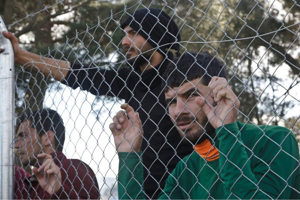 Migrants wait behind a chain link fence at the northern Greek border station of Idomeni, Tuesday, March 8, 2016. Up to 14,000 people are stranded on the outskirts of the village of Idomeni, with more than 36,000 in total across Greece, as EU leaders who held a summit with Turkey on Monday said they hoped they had reached the outlines of a possible deal with Ankara to return thousands of migrants to Turkey. (AP Photo/Visar Kryeziu)