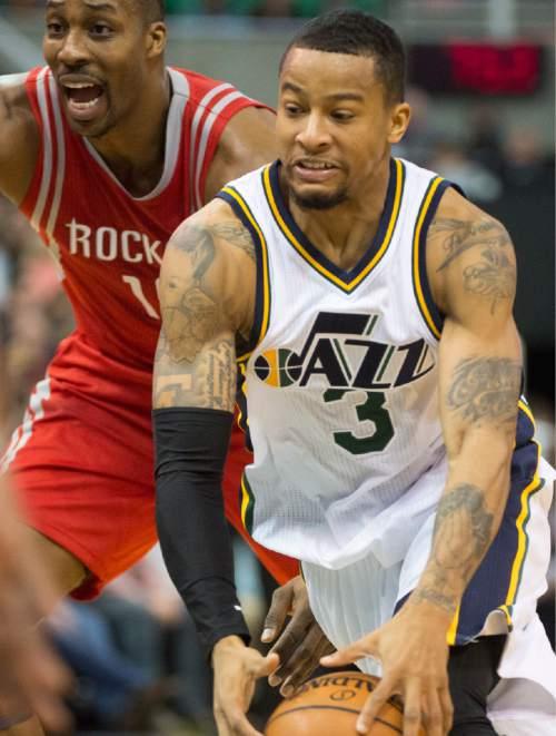 Rick Egan  |  The Salt Lake Tribune  Utah Jazz guard Trey Burke (3) gets past Houston Rockets center Dwight Howard (12), in NBA action, The Utah Jazz vs. The Houston Rockets, in Salt Lake City, Monday, January 4, 2016.