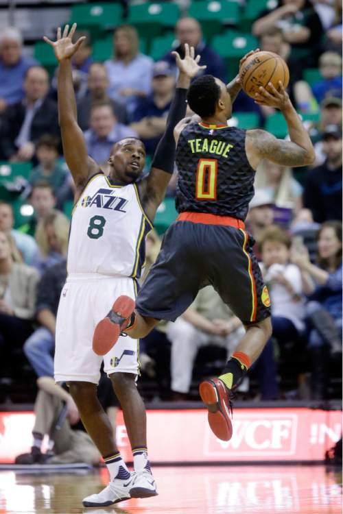 Atlanta Hawks guard Jeff Teague (0) shoots as Utah Jazz guard Shelvin Mack (8) defends during the first quarter of an NBA basketball game Tuesday, March 8, 2016, in Salt Lake City. (AP Photo/Rick Bowmer)