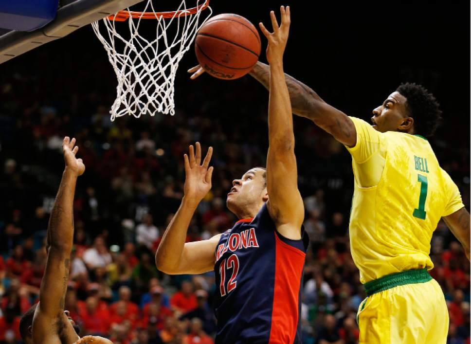 Oregon forward Jordan Bell (1) knocks the ball out of the hands of Arizona forward Ryan Anderson (12) during the first half of an NCAA college basketball game in the semifinal round of the Pac-12 men's tournament Friday, March 11, 2016, in Las Vegas. (AP Photo/John Locher)