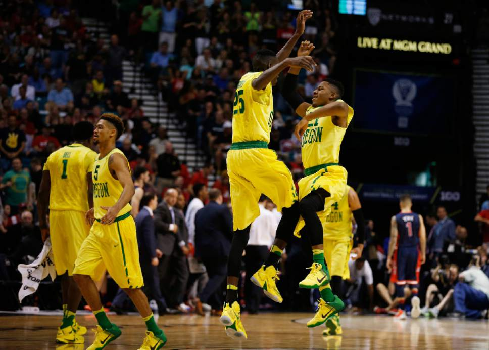 Oregon guard Kendall Small, right, and forward Chris Boucher (25) jump into the air in celebration during the first half of an NCAA college basketball game against Arizona in the semifinal round of the Pac-12 men's tournament Friday, March 11, 2016, in Las Vegas. (AP Photo/John Locher)