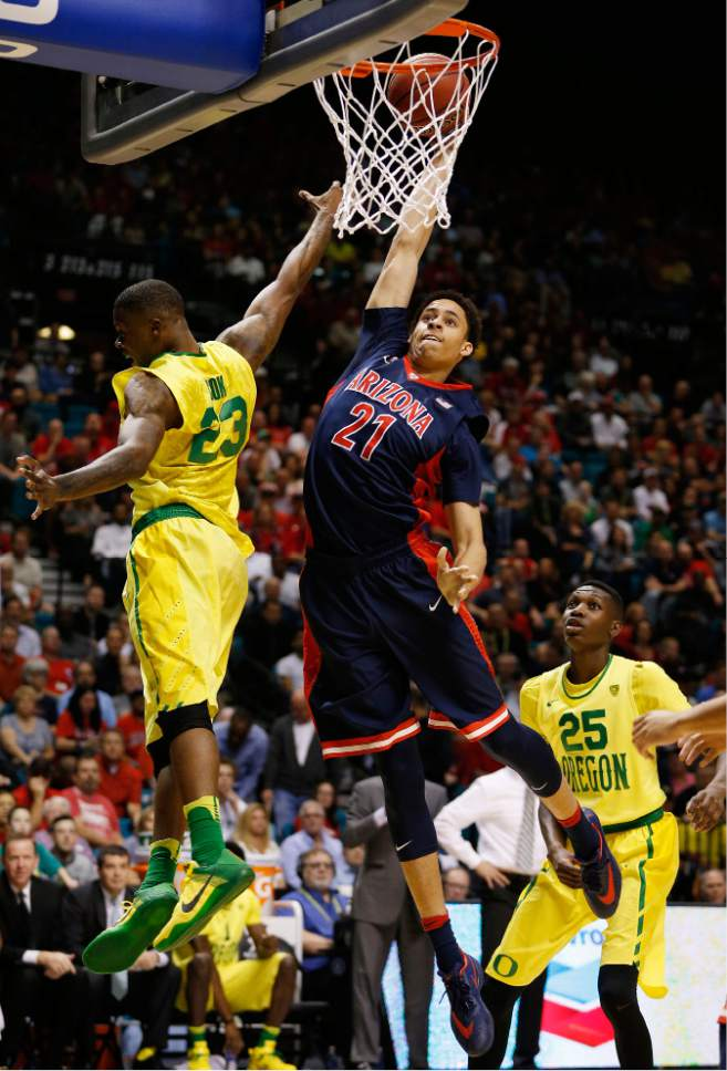 Arizona center Chance Comanche dunks over Oregon forward Elgin Cook, left, during the first half of an NCAA college basketball game in the semifinal round of the Pac-12 men's tournament Friday, March 11, 2016, in Las Vegas. (AP Photo/John Locher)