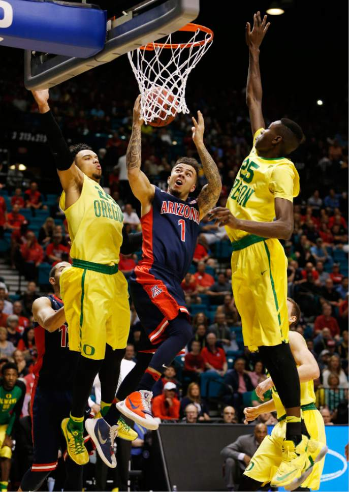 Arizona guard Gabe York (1) shoots between Oregon forwards Dillon Brooks (24) and Chris Boucher (25) during the first half of an NCAA college basketball game in the semifinal round of the Pac-12 men's tournament Friday, March 11, 2016, in Las Vegas. (AP Photo/John Locher)