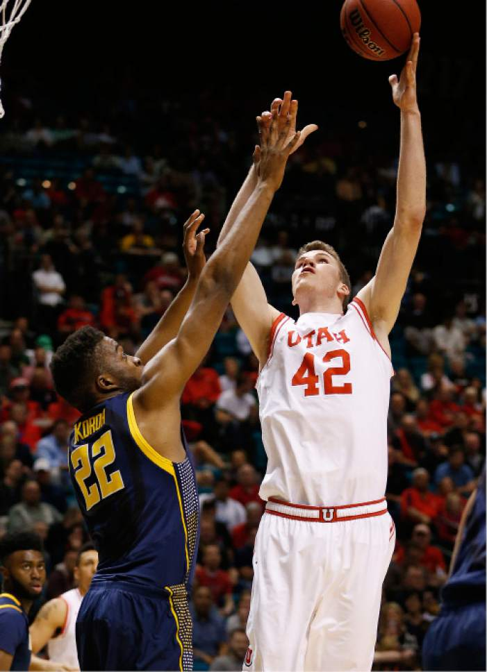 Utah forward Jakob Poeltl shoots over California center Kingsley Okoroh during the first half of an NCAA college basketball game in the semifinals of the Pac-12 men's tournament Friday, March 11, 2016, in Las Vegas. (AP Photo/John Locher)