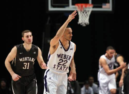Weber State fguard Ryan Richardson (22) holds up three fingers after scoring a 3-point basket against Montana in the first half of an NCAA college basketball game for the championship of the Big Sky conference men's tournament in Reno, Nev., Saturday, March 12, 2016. (AP Photo/Lance Iversen)