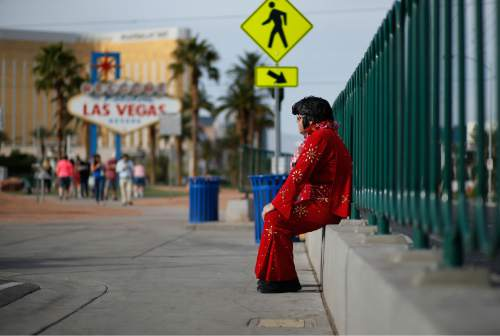 """In this March 3, 2016, photo, Ted Payne rests as he works for tips dressed as Elvis at the """"Welcome to Las Vegas"""" sign in Las Vegas. For decades, Las Vegas has loved Elvis Presley. But the King's presence in modern day Sin City has lately been diminishing. (AP Photo/John Locher)"""