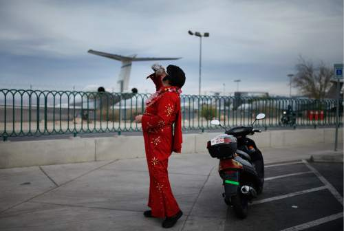 """In this March 3, 2016, photo, Ted Payne takes a drink as he works for tips dressed as Elvis at the """"Welcome to Las Vegas"""" sign in Las Vegas. For decades, Las Vegas has loved Elvis Presley. But the King's presence in modern day Sin City has lately been diminishing. (AP Photo/John Locher)"""