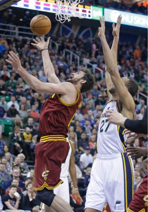 Cleveland Cavaliers forward Kevin Love, left, lays the ball up as Utah Jazz center Rudy Gobert (27) defends during the first quarter of an NBA basketball game Monday, March 14, 2016, in Salt Lake City. (AP Photo/Rick Bowmer)