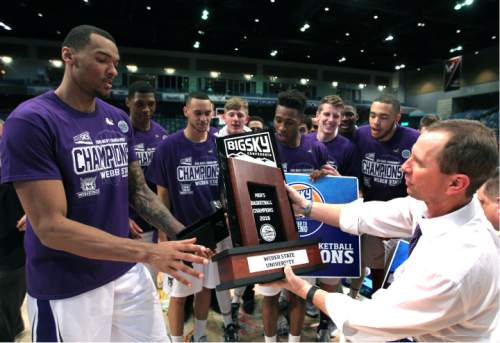 Weber State coach Randy Rahe, right, hands off the team trophy to forward Joel Bolomboy (21) after Weber State won the Big Sky men's tournament championship, defeating Montana 62-59 in an NCAA college basketball game in Reno, Nev., Saturday, March 12, 2016. (AP Photo/Lance Iversen)