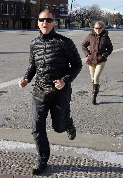 "Dell ""Super Dell"" Schanze runs as he arrives for a court appearance at the federal courthouse Tuesday, Dec. 30, 2014, in Salt Lake City. Schanze, a former Utah TV pitchman is accused of kicking an owl while riding his motorized paraglider says he will allow authorities to search his home for guns as a condition of his pretrial release. (AP Photo/Rick Bowmer)"