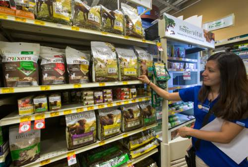In this Wednesday, March 16, 2016, photo, PetSmart customer engagement leader Moni Contreras shows one of the premium dog foods at the PetSmart Midtown store in Los Angeles. Americans spent just over $60 billion on their pets in 2015, a record fueled by a big jump in what owners shelled out for services like grooming, boarding and training. (AP Photo/Damian Dovarganes)