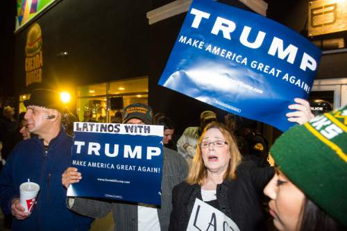 Chris Detrick     The Salt Lake Tribune Supporters of Republican presidential candidate Donald Trump hold up a sign outside of the Infinity Event Center Friday March 18, 2016.