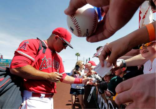 Los Angeles Angels' Mike Trout signs autographs prior to a spring training baseball game against the Seattle Mariners, Tuesday, March 15, 2016, in Tempe, Ariz. (AP Photo/Matt York)