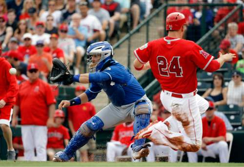 Los Angeles Angels' C.J. Cron slides safely past Kansas City Royals catcher Tony Cruz during the second inning of a spring training baseball game Sunday, March 6, 2016, in Tempe, Ariz. Cron scored from third on a sacrifice fly by Carlos Perez. (AP Photo/Morry Gash)
