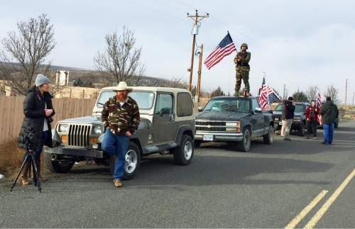 People protesting the FBI action and in support of the armed occupiers of the Malheur National Wildlife Refuge stand outside a roadblock near Burns, Ore., Thursday, Feb. 11, 2016. The last four occupiers of a national wildlife refuge in eastern Oregon surrendered Thursday. The holdouts were the last remnants of a larger group that seized the wildlife refuge nearly six weeks ago, demanding that the government turn over the land to locals and release two ranchers imprisoned for setting fires. (AP Photo/Rebecca Boone)