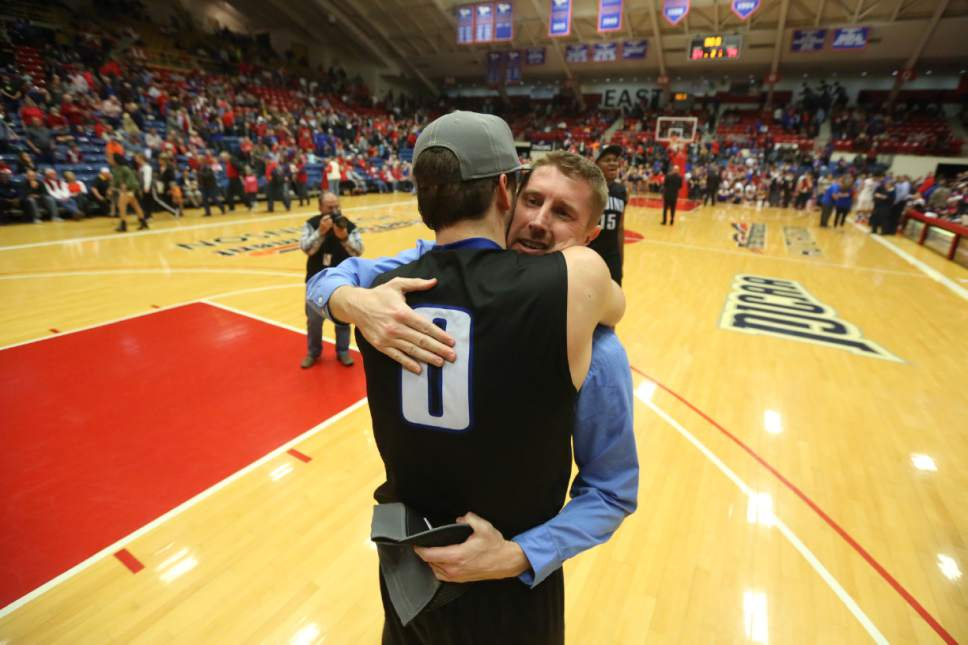 Salt Lake's Gibson Johnson hugs coach Todd Phillips after the team won the NJCAA tournament 74-63 over Hutchinson on Saturday, March 19, 2016, in Hutchinson, Kan. (Travis Morisse/The Hutchinson News via AP)
