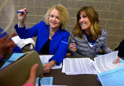 Leah Hogsten  |  The Salt Lake Tribune l-r  Salt Lake City Mayor Jackie Biskupski and Ashley Hoopes help voters to the ballot box.  Lines and wait times were long at the Democratic caucus at Clayton Middle School as both registered party members and unaffiliated voters cast their ballots, Tuesday, March 22, 2016.