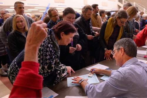 Leah Hogsten  |  The Salt Lake Tribune Julie Jensen (center) wound up in the wrong line because of her cataracts, but eventually got her ballot. Lines and wait times were long at the Democratic caucus at Clayton Middle School as both registered party members and unaffiliated voters cast their ballots, Tuesday, March 22, 2016.
