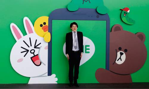 A man poses for a photo in front of Line Corp. logo with its popular animal characters during a press conference of Line Conference Tokyo 2016 in Urayasu, near Tokyo, Thursday, March 24, 2016. Although social media companies have struggled to gain revenue, Line, now used in 230 nations, including Asia, South America and Africa, has succeeded in unusual ways, such as merchandising of its mascot-like characters as dolls, which are sold in real stores. (AP Photo/Shizuo Kambayashi)
