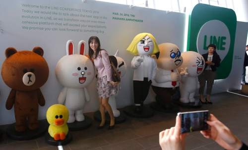 Visitors pose for a photo in front of Line Corp. logo and its popular characters during a press conference of Line Conference Tokyo 2016 in Urayasu, near Tokyo, Thursday, March 24, 2016. Although social media companies have struggled to gain revenue, Line, now used in 230 nations, including Asia, South America and Africa, has succeeded in unusual ways, such as merchandising of its mascot-like characters as dolls, which are sold in real stores. (AP Photo/Shizuo Kambayashi)