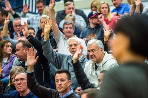 Chris Detrick  |  The Salt Lake Tribune Voters in precinct 13 raise their hands to indicate they have not yet received a presidential ballet during the Republican caucus at Corner Canyon High School Tuesday March 22, 2016.