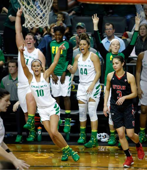 Utah's Malia Nawahine transitions back on offense as Oregon's Lexi Bando celebrates with her teammates after Bando drained one of her six three-pointers that helped lead the Ducks to a 73-63 win over Utah in the WNIT Sweet 16 game at Matthew Knight Arena in Eugene. Bando had 34 total points in the game as the Ducks move onto the Round of 8. (Andy Nelson/The Register-Guard)