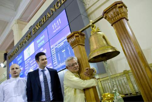 Serge Pun, right, executive chairman of First Myanmar Investment joyfully hugs a bell pillar as electronic trading commence listing his company during the opening day of trading at Yangon Stock Exchange in Yangon, Myanmar, Friday, March 25, 2016. Myanmar's new stock exchange, the Yangon Stock Exchange (YSX) officially opened for business on Friday more than three months after it was launched in December 2015.(AP Photo/ Gemunu Amarasinghe)