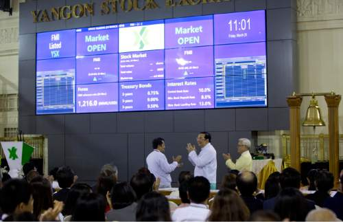 Serge Pun, far right executive chairman of First Myanmar Investment Maung Maung Thein, center Deputy Minister of Finance and Revenue applued after ringing the bell to commence electronic trading during the opening day of trading at Yangon Stock Exchange in Yangon, Myanmar, Friday, March 25, 2016. Myanmar's new stock exchange, the Yangon Stock Exchange (YSX) officially opened for business on Friday more than three months after it was launched in December 2015.(AP Photo/Gemunu Amarasinghe)