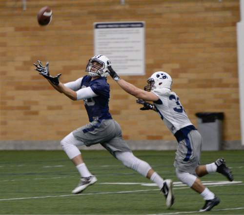 Francisco Kjolseth  |  The Salt Lake Tribune  BYU football opens spring camp on Monday, March 2, 2015, with indoor practice at the Smith Fieldhouse as Josh Weeks reaches out for a pass with Eric Takenaka defending.