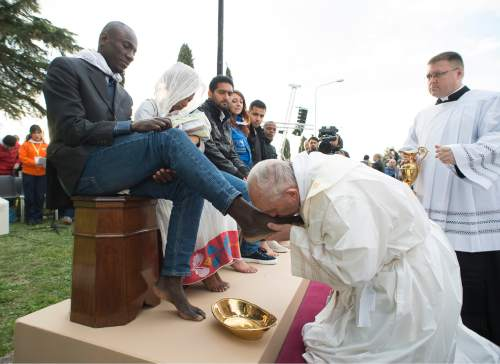 Pope Francis kisses the foot of a man during the foot-washing ritual at the Castelnuovo di Porto refugees center, some 30km (18, 6 miles) from Rome, Thursday, March 24, 2016. The pontiff washed and kissed the feet of Muslim, Orthodox, Hindu and Catholic refugees Thursday, declaring them children of the same God, in a gesture of welcome and brotherhood at a time when anti-Muslim and anti-immigrant sentiment has spiked following the Brussels attacks. (L'Osservatore Romano/Pool Photo via AP)