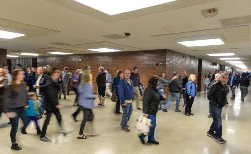 Francisco Kjolseth | The Salt Lake Tribune Navigating a complicated layout of various rooms for their precincts, republicans roam the halls of Cottonwood High School for the GOP caucus on Tuesday night, March 22, 2016.