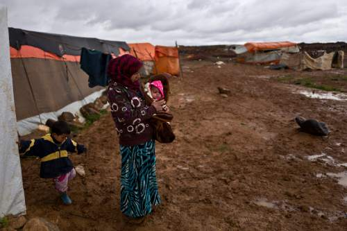 A Syrian refugee holds her daughter while standing outside her tent during a rainfall at an informal tented settlement near the Syrian border, on the outskirts of Mafraq, Jordan, Monday, March 28, 2016. (AP Photo/Muhammed Muheisen)