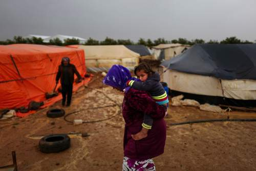A Syrian refugee carries her child as she heads back to her tent through muddy slippery ground during a rainfall at an informal tented settlement near the Syrian border, on the outskirts of Mafraq, Jordan, Monday, March 28, 2016. (AP Photo/Muhammed Muheisen)