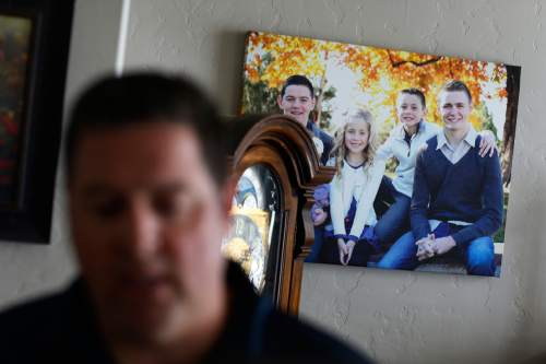 A picture of Mason Wells, on the right on the photo hanging on the wall, is on display as Mason Wells' father Chad Wells talks about him Tuesday, March 22, 2016, in Sandy, Utah. The bombs that tore through the Brussels airport Tuesday seriously wounded three Mormon missionaries including his son, and sent a French missionary from their group to the hospital, church officials said. (AP Photo/John Locher)