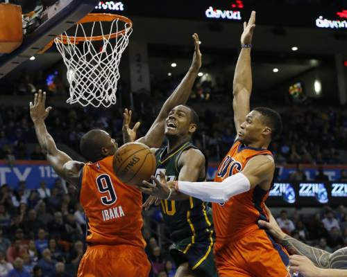 Oklahoma City Thunder guard Russell Westbrook, right, knocks the ball away from Utah Jazz guard Alec Burks, center, as he shoots between Westbrook and forward Serge Ibaka (9) in the fourth quarter of an NBA basketball game in Oklahoma City, Sunday, Dec. 13, 2015. Oklahoma City won 104-98 in overtime. (AP Photo/Sue Ogrocki)