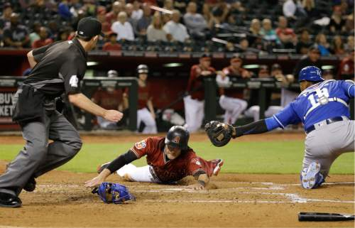 Arizona Diamondbacks' A.J. Pollock, center, avoids a tag from Kansas City Royals catcher Salvador Perez, right, to score on a hit by David Peralta during the third inning of a spring training baseball game Friday, April 1, 2016, in Phoenix. (AP Photo/Jae C. Hong)