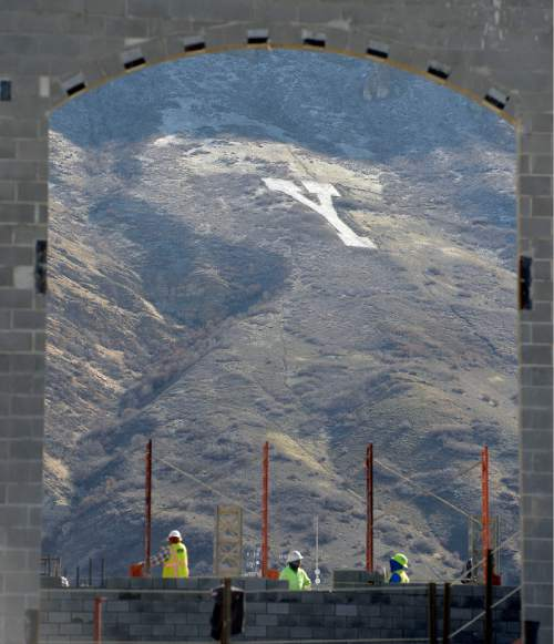 "Al Hartmann  |  The Salt Lake Tribune Sun lights up ""Y"" on the rugged mountain face east of the BYU campus as construction workers build a new student apartment building Wednesday March 16."