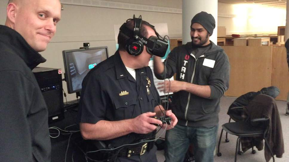 """   Courtesy Jed Merrill  Lt. Wade Bruer of Utah's police academy (center), with developer Eric Allen (left) and engineer Nidal Ilyas (right), test """"B.E.S.T. Police Training,"""" a virtual-reality simulator that tests officers' de-escalation skills."""