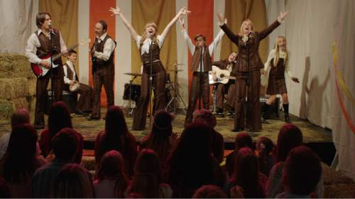 """Courtesy photo The Flinders Family - from left: Kenny Holland, Ethan Mouser, Brian Neal Clark, Monica Moore Smith, Bailie Johnson, rear, on drums, Jacob Buster, Anna Daines, Alison Akin Clark and Caroline Labrum - perform in a scene from the movie version of the LDS musical """"Saturday's Warrior."""""""