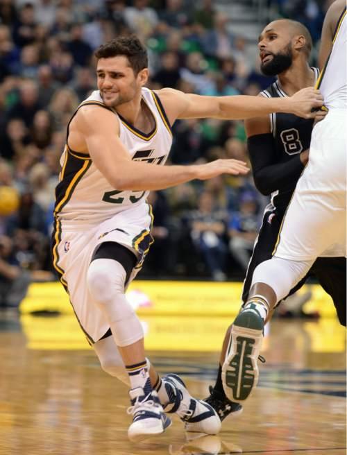 Steve Griffin  |  The Salt Lake Tribune   Utah Jazz guard Raul Neto (25) struggles to get free of San Antonio Spurs guard Patty Mills (8) during the Jazz versus Spurs NBA basketball game at Vivint Smart Home Arena in Salt Lake City, Tuesday, April 5, 2016.