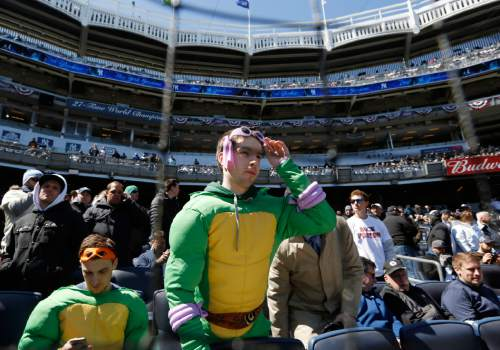 """Joe Spillo, left, looks at his cell phone while John Welch, both of Yorktown Heights, N.Y., looks around from their pricey Legends Suites luxury seats behind home plate before an opening day baseball game between the New York Yankees and the Houston Astros in New York, Tuesday, April 5, 2016. The pair were awarded the normally high-priced seats for 25 cents for being """"poorly dressed"""" by television personality John Oliver. (AP Photo/Kathy Willens)"""