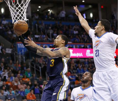 Utah Jazz guard Trey Burke (3) shoots in front of Oklahoma City Thunder guard Dion Waiters, center, and Thunder's Andre Roberson (21) during the fourth quarter of an NBA basketball game in Oklahoma City, Thursday, March 24, 2016. Oklahoma City won 113-91. (AP Photo/Sue Ogrocki)