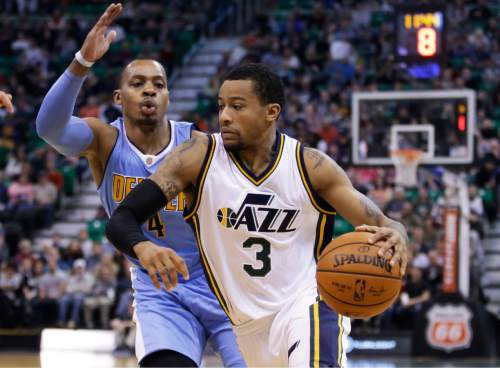 Utah Jazz guard Trey Burke (3) drives around Denver Nuggets guard Randy Foye (4) during the second half of an NBA basketball game Friday, Dec. 18, 2015, in Salt Lake City. The Jazz won 97-88. (AP Photo/Rick Bowmer)